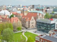 Aerial view of the University campus, showing Gilbert square, the modern architecture of the Learning Commons beside grand old buildings such as Whitwoth Hall and the tower. Manchester skyline in the background.